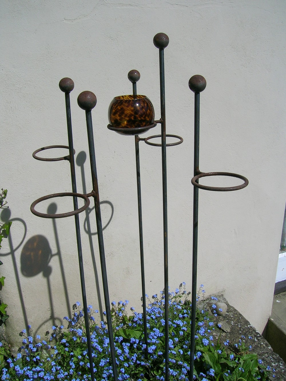 Outdoor candle holders support 4 plants designed to be hammered down into the ground